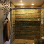Esmerald Onyx Slab Shower with a Fossil Green Limestone one piece shower base. The bathroom floor is Gold Travertine cut to resemble wood planking